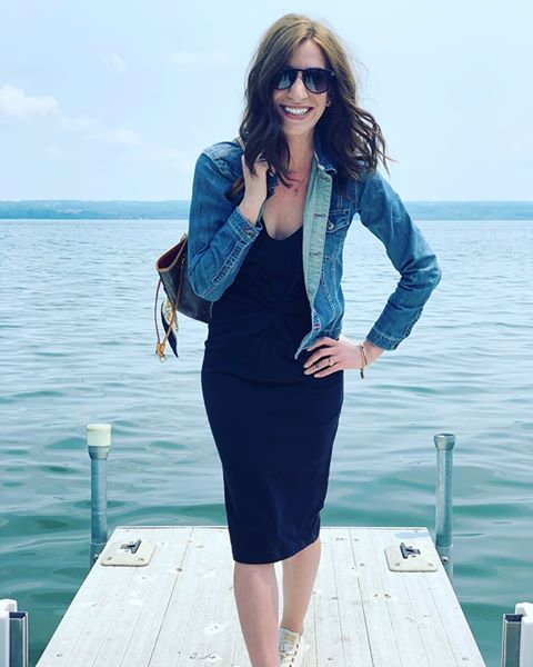 Kelsey is standing at the end of a small pier smiling at the camera. She has light skin, medium-long brown hair. She is wearing a black knee-length dress with a denim jacket, and big sunglasses.