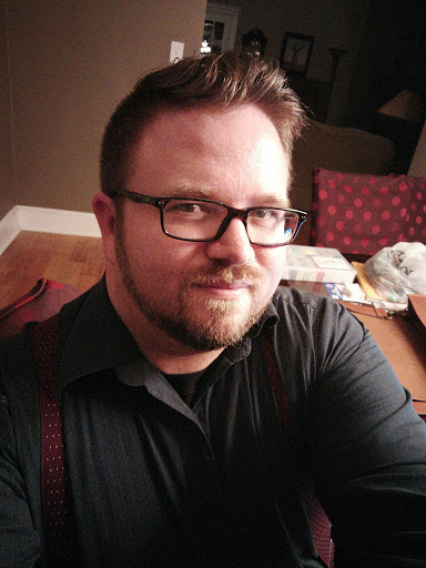 Ford is taking a selfie in his dining room. He has light skin, glasses, and a beard and mustache. He is looking at the camera with a soft smile and is wearing a black button up long sleeve shirt with purple suspenders with white dots.